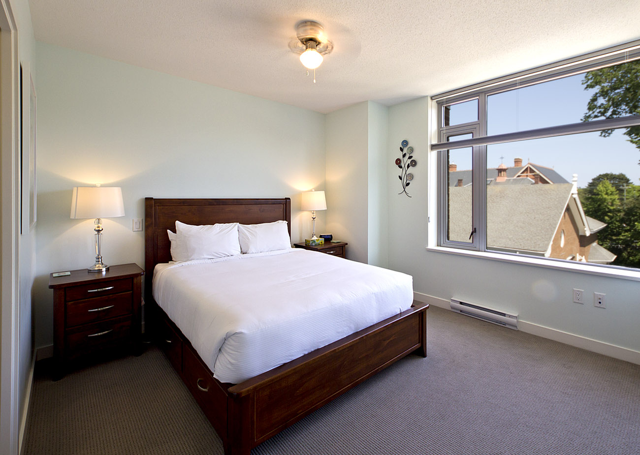 furnished bedroom with queen bed and large window